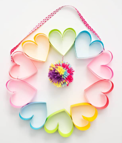 Rainbow paper heart wreath with a colorful pompom on the middle