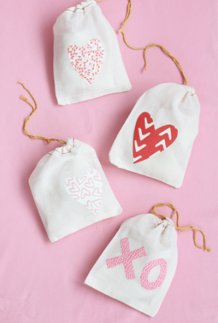 muslin drawstring treat bags with hearts and XO printed on them