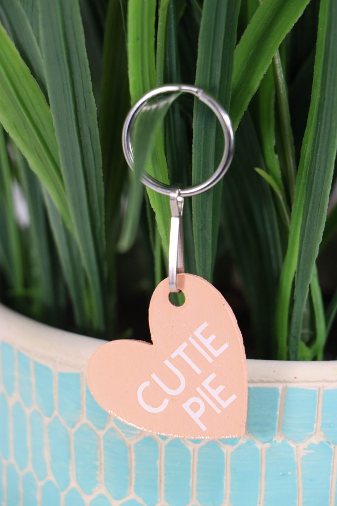 A heart shaped keychain with text saying cutie pie