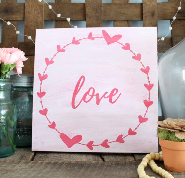 farmhouse style wooden sign with a circle of hearts and the word love in the center of the circle