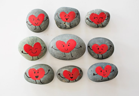 Different shape rocks painted red heart shape with different smiley faces on it using a fingerprint