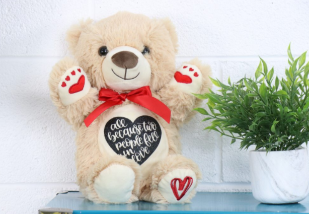 teddy bear with heart on his belly saying All because two people fell in love