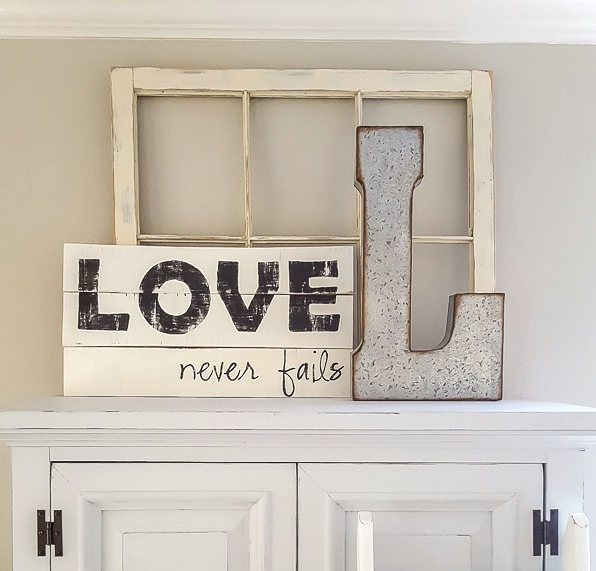 Farmhouse style wooden signs one says Love never fails and the other one is letter L