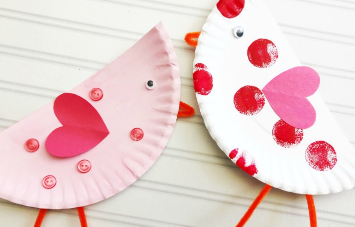 Paper plate love birds one is a color white with red paint circles and pink heart shape the other is a color pink with a red heart shape and color pink buttons on it