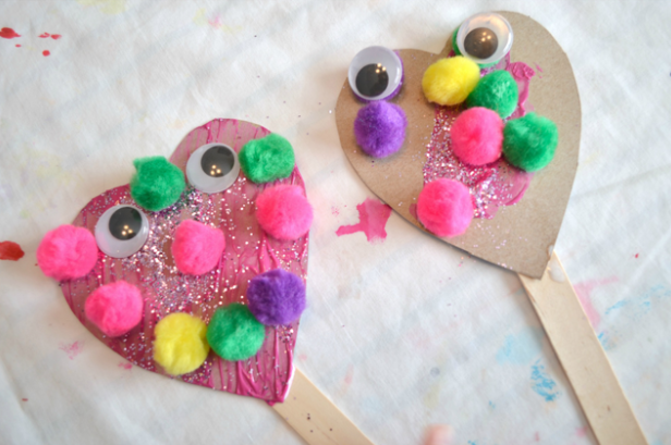 Silly heart puppet with some colorful puffballs on it.