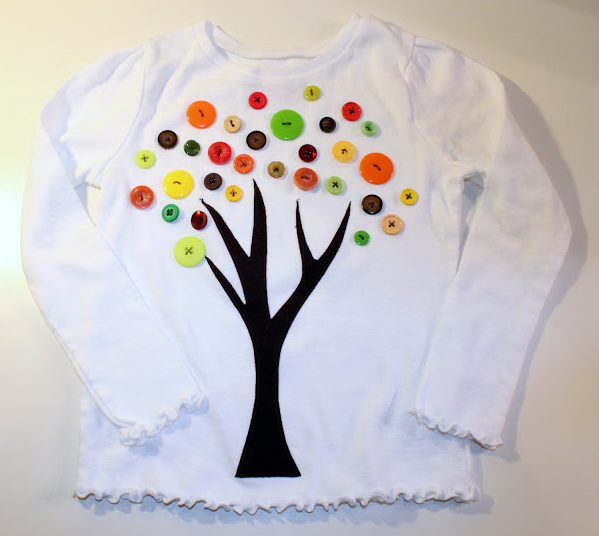 tshirt with a tree trunk painted on and 100 buttons as leaves