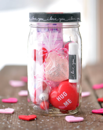 mason jar filled with items like chapstick, bath bombs, and candy - rim of jar says I love you over and over on it