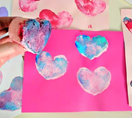 Pink paper sponge painted with lovely colors heart shapes on it.