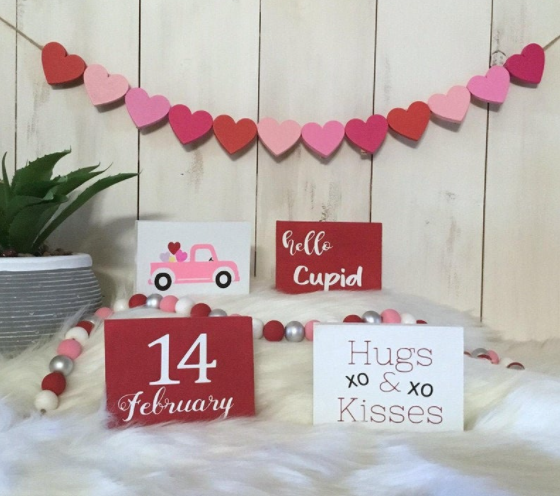 a valentine banner and four valentine's sign- one say hugs xo and xo kisses, second says hello cupid, third says 14 February , fourth has a color pink vintage truck