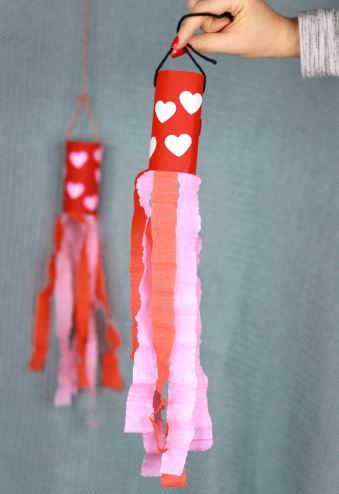 Valentine's day windsock made from a toilet paper roll painted red with heart shapes on it and a pink and red tissue paper strips on it.