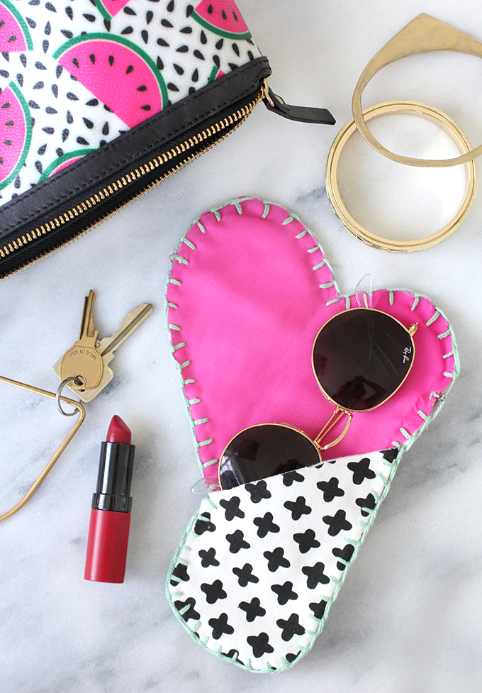 Heart shaped sunglasses case with a sunglasses on it, a coupe of key, a red lipstick and a watermelon designed pouch
