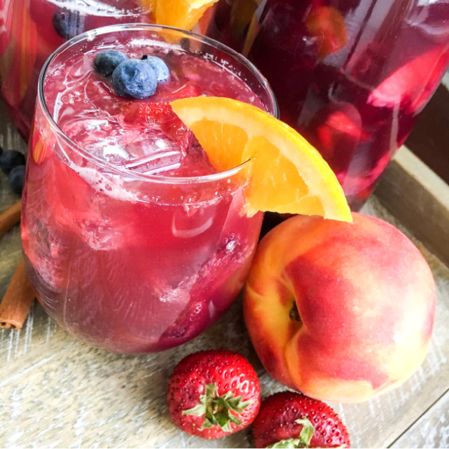 Berry peach sparkling sangria on a glass with an orange wedge