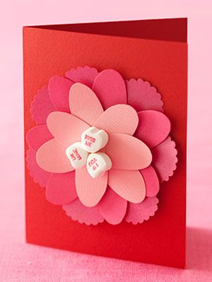 Valentine's day card with flower petals and candy hearts on the middle