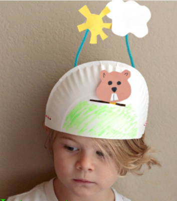 half a paper plate crown with paper groundhog and paper sun and cloud sticking up from it