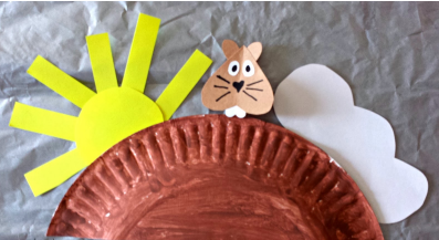 painted half a paper plate as groundhog's home, with paper groundhog, sun, and cloud