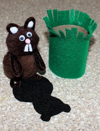 pompom groundhog with felt features, felt shadow, and felt covered tube for groundhog's grassy hole
