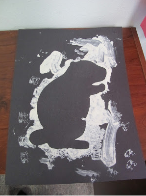 black paper with white paint to create outline of a groundhog
