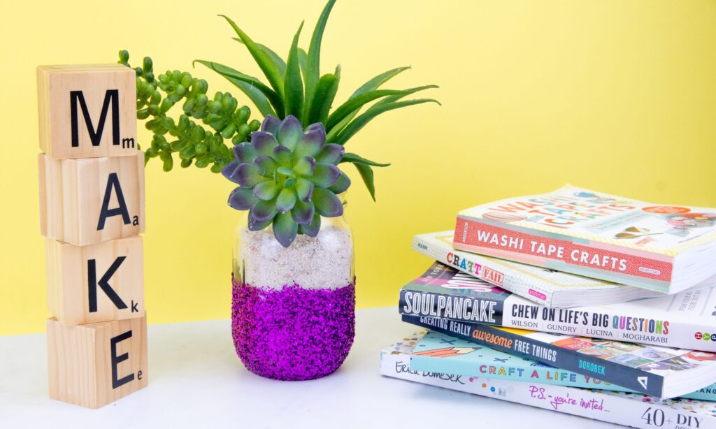 Diy glitter vase made from a mason jar covered half with purple glitter and a succulents plant coming out of the jar