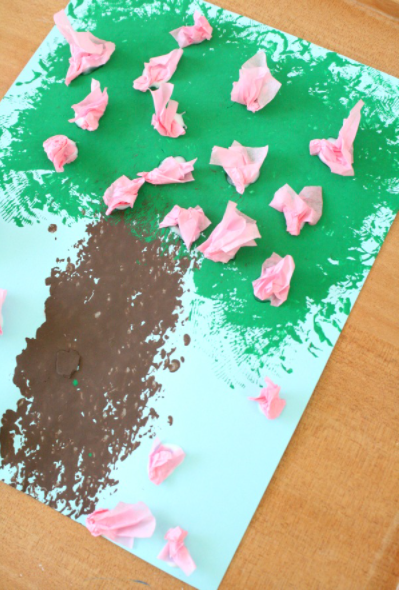 A spring painted tree with a pink DIY flowers made from a crumble pink tissue paper