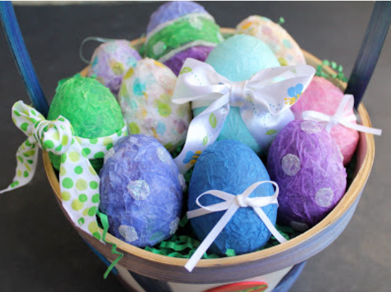 Plastic Easter egg covered with assorted colors of tissue paper with glitters and ribbon.
