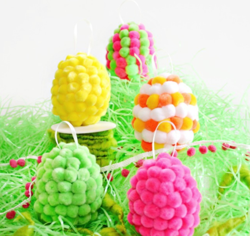 Plastic Easter eggs covered with colorful pompoms and a ribbon on top.