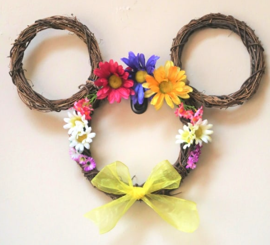 Mickey mouse shaped flower wreath with a different silk flowers on it and a yellow ribbon in the middle