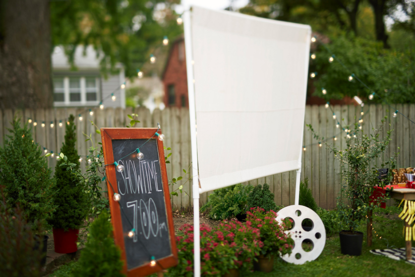 A homemade outdoor movie screen made of pvc pipes and drop cloth for backyard theater