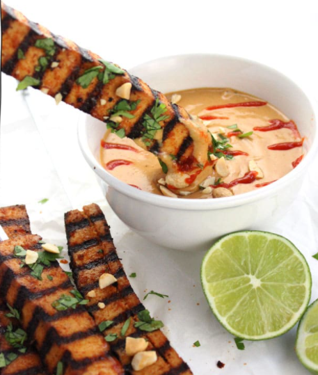 Grilled tofu skewers with spicy peanut sauce and lime on the side