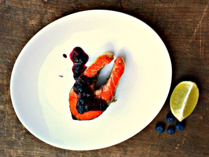 Grilled Cedar Planked Sockeye Salmon with Maple Blueberry Chutney on top and lemon on the side of the plate