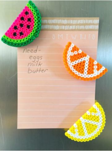 Perler bead magnets that looks like a watermelon that has different colors; orange, yellow and green.