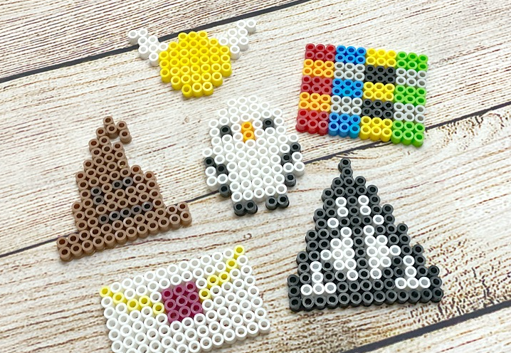 Harry Potter themed perler beads. The designs are Deathly Hallows, a Sorting Hat, a Golden Snitch, an Owl, a Hogwarts Letter, and House Colors.