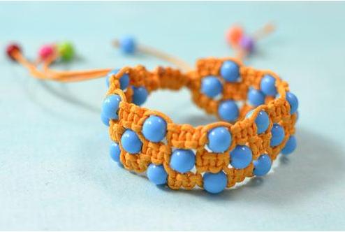 A cute orange square knot friendship bracelet with blue acrylic beads