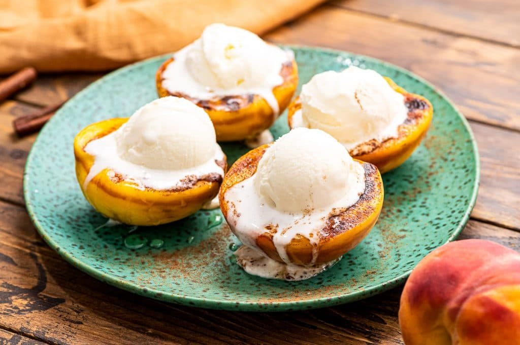 Grilled peaches top with cinnamon, honey and a scoop of ice cream a perfect summer dessert