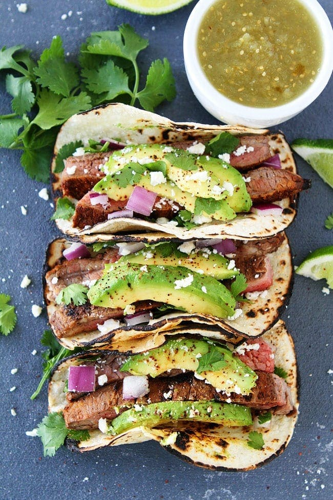 Grilled steak tacos with red onion, avocado, cilantro, and queso fresco for the summer