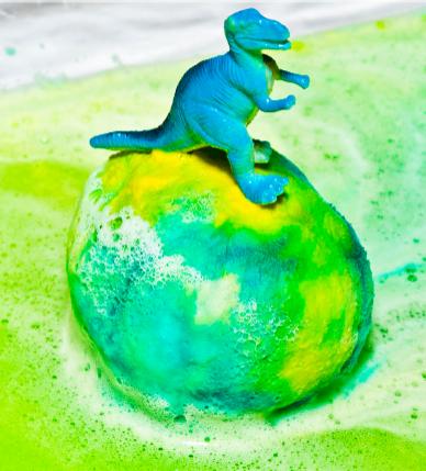 Um dinossauro em cima de um ovo de dinossauro coberto com bicarbonato de sódio colorido
