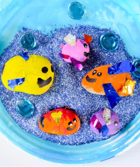 A colorful painted rock fish craft and play idea for kids this summer