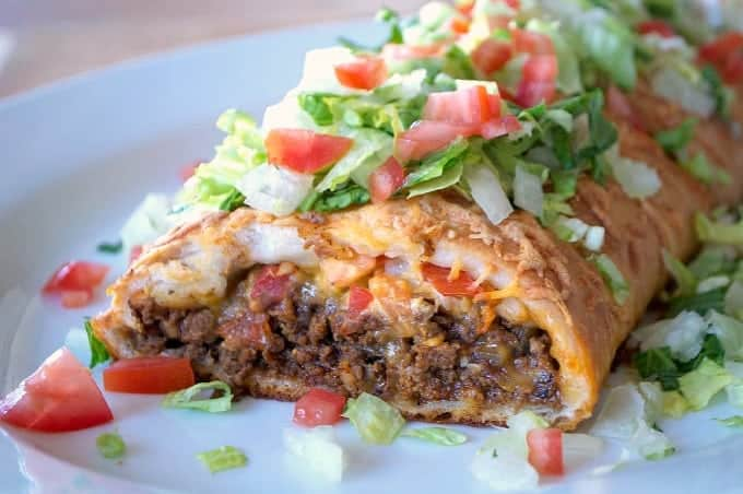 A taco made with ground beef cheese tomatoes wrapped in braided pizza dough
