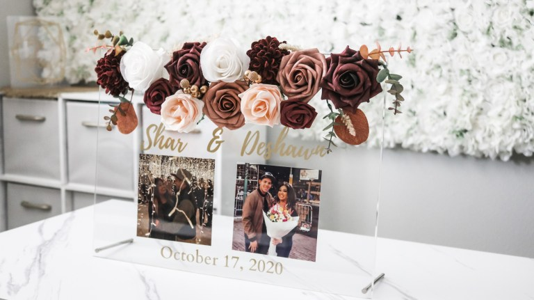 Beautiful acrylic wedding sign with the bride and groom name and photos and the wedding date