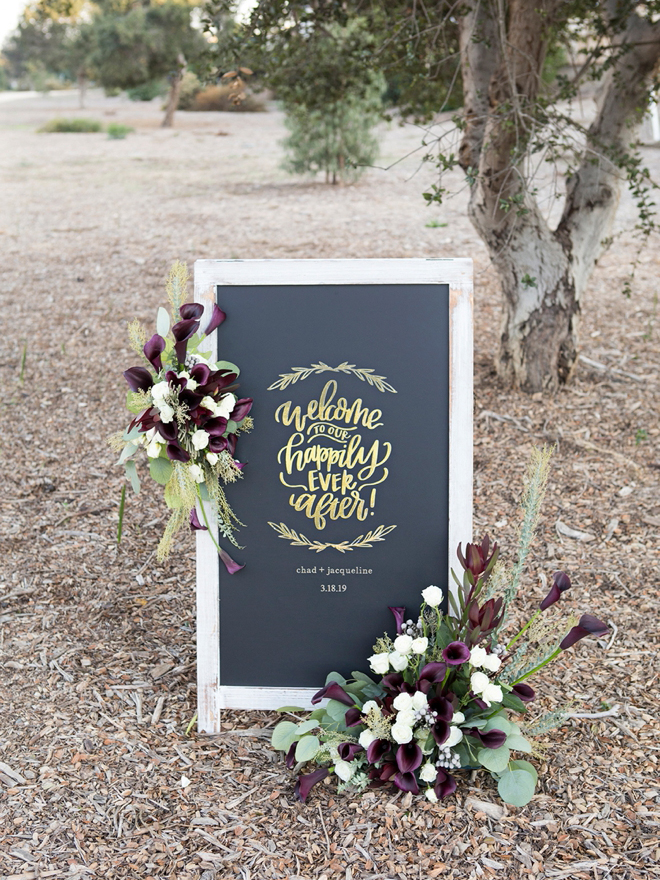 DIY wedding sign says welcome to our happily ever after Chad + Jacqueline 3.18.19 with flower arrangement on it