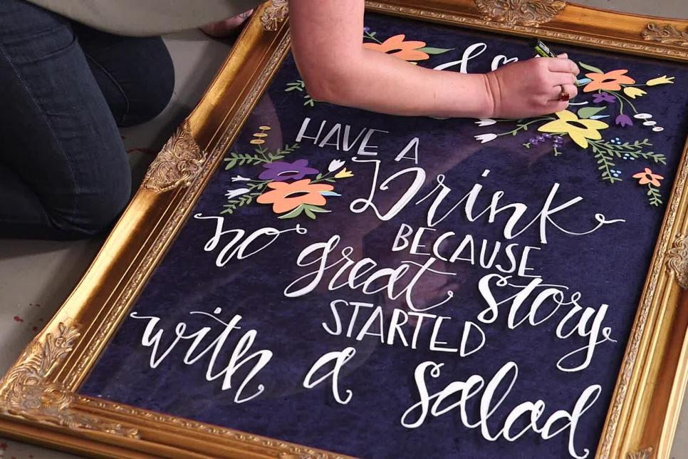 hand lettered wedding sign with random beautiful flowers design on it and text saying Have a drink because no great story started with a salad