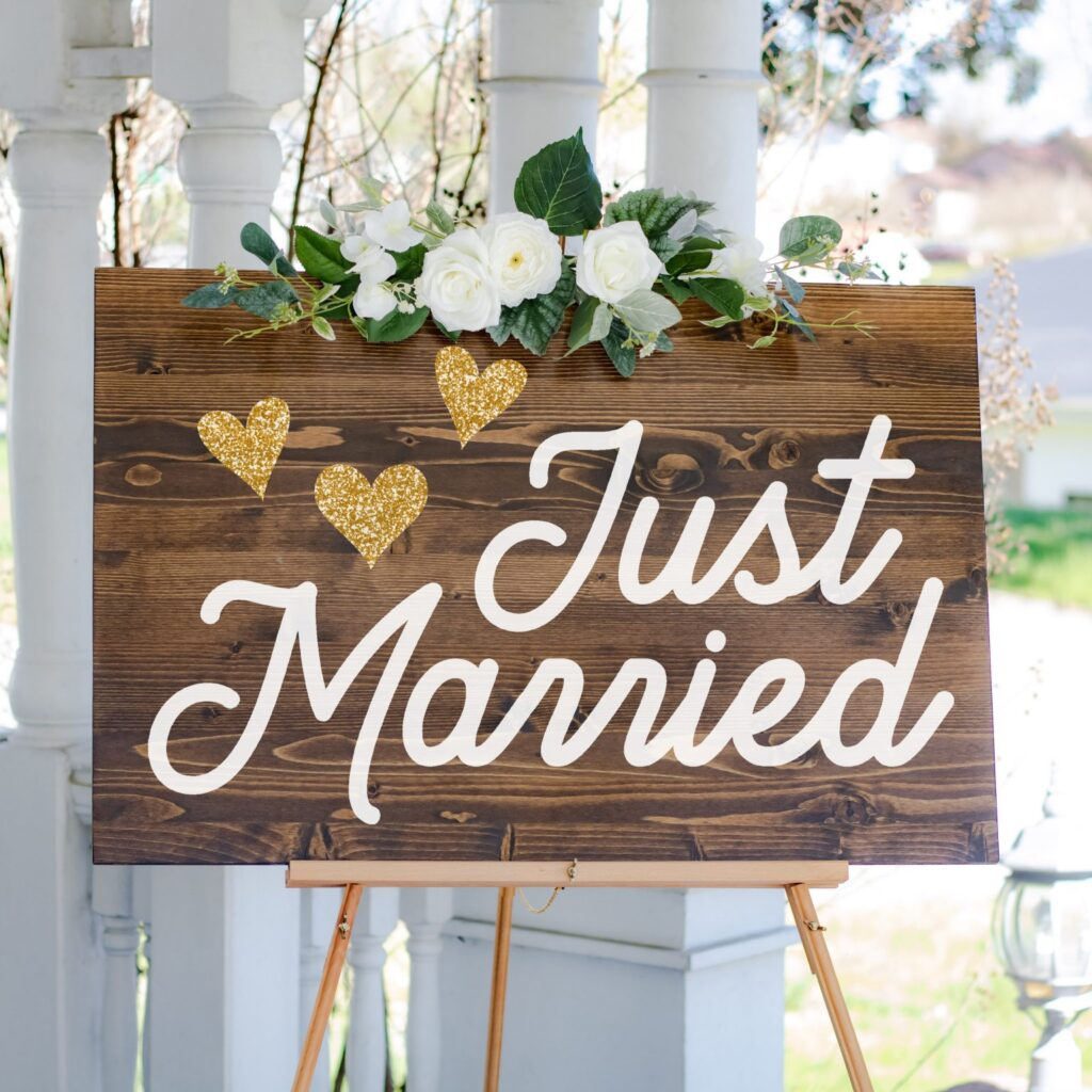 Gorgeous wedding sign says just married with three gold hearts on it and a white roses decorations above