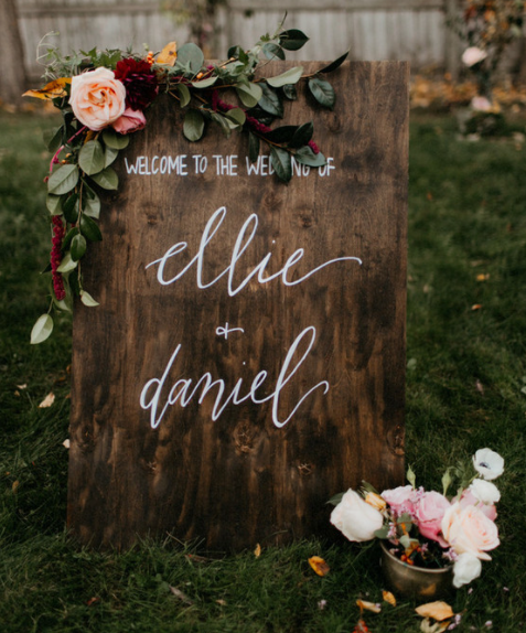 Calligraphy wedding sign on a wood that says Welcome to the wedding of Ellie & Daniel with flower arrangement on it