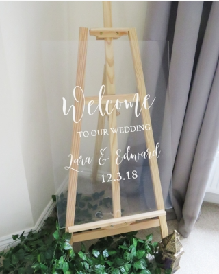 Welcome wedding sign made from a glass board with text saying welcome to our wedding Lara & Edward 12.3.18