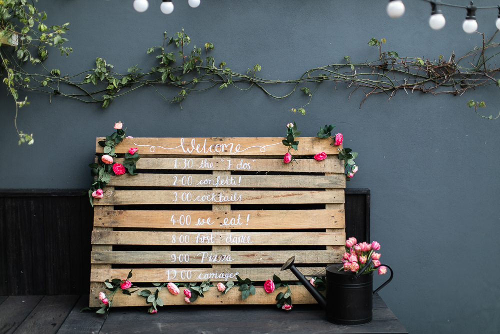 Wooden pallet wedding sign that indicates the wedding schedule