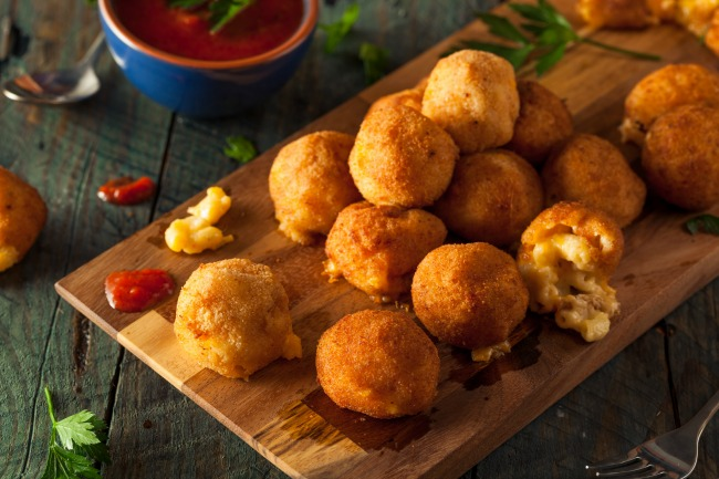 baked mac and cheese bites served with a delicious marinara dipping sauce
