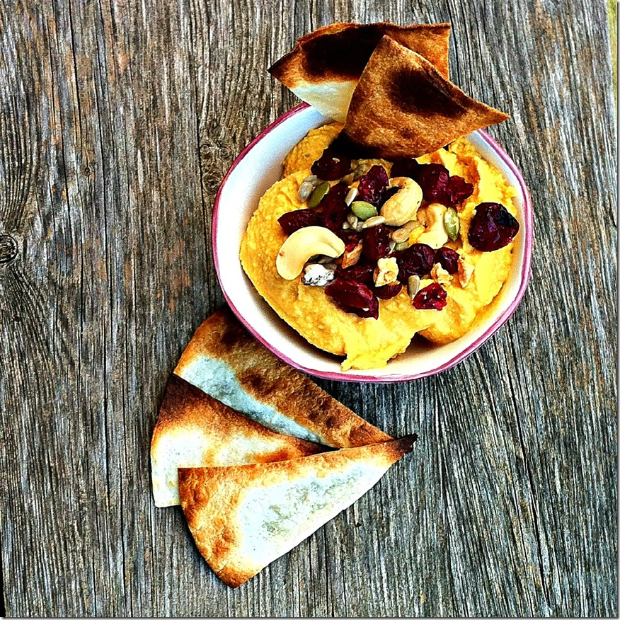 Pumpkin hummus topped with a fall snack mix and tortilla chips