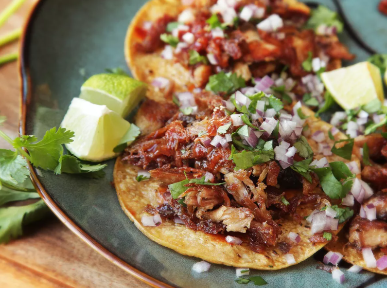 Leftover turkey carnitas top with chopped red onions and a slice of lime on the side